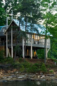 """This interior designer's modern lake house is was described once as a """"wonderful glassy box on wooden sticks"""", hovering like a tree-house. The structure is sympathetically tucked into the slash pines using seven telephone poles twenty to forty feet in height. The poles were arranged randomly to refl"""