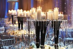 Go glam! Create your own modern centerpiece that sparkles from every angle by combining tall pillars, dazzling crystal accents, and rhinestone-accented glass candle holders. #weddingcenterpiece #weddings