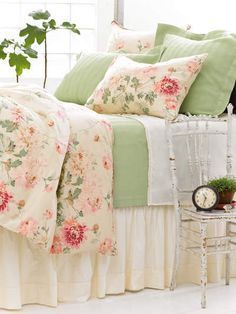 A well made bed with a floral comforter on top ~
