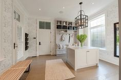 source: Pricey Pads      Huge mudroom with white built-in locker cabinet with beadboard backsplash, row of hooks and built-in bench. Iron lantern over mudroom island over staggered tile floor. Mudroom design features floral wallpaper, Herman Miller Nelson Bench.
