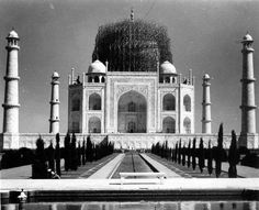 This was how the Taj Mahal was protected from bomber jets in 1942 during world war.  It was covered with huge scaffold, to make it look like a stockpile of bamboo and misguide bombers.  The covering is still incomplete in this photo. The whole of Taj Mahal was covered but this picture shows only the main dome covered. During the India-Pakistan war in 1971, it was protected by covering it with a green cloth and making it almost invisible i.e. camouflaged within the greenery around it.