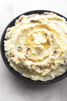 mashed potatoes with butter melting in a black bowl