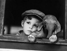 A boy and elephant- This is a vintage photo and as such this may very well be a circus pair. Those were terrible times for elephants but this little one looks happy with his friend!