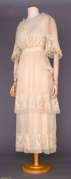 """3 SUMMER TEA GOWNS, 1914-1918 Go Back Lot: 355 May 9, 2017 - CATALOG SALE Sturbridge, Massachusetts 1 empire in white lawn w/ pink embroidered rose buds near W, tulle & lace bodice, B to 38, W 25"""", L 52"""", (few tiny holes) very good; 1 ecru tulle over cream silk satin, lace bodice & skirt bottom lavishly embroidered & w/ Brussels lace trim, B to 38"""", W to 29"""", L 55"""", (shredded sash, stains on satin by H) very good; 1 cream tulle, bodice & 2-tier skirt w/ lace trim,"""