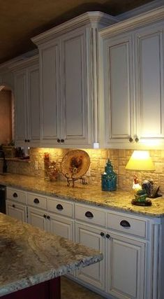 Distressed white cabinets and under cabinet lighting.