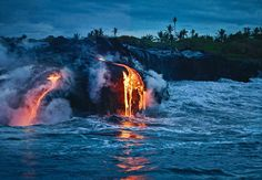 Molten lava from a volcano seeps into the ocean water of Hawaii