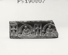 Part of a panel with a caitya arch frieze of seated monks in two compartments. Each compartment contains a monk in dhyāna, his hands covered, his robe with grooves for drapery folds and his head turned in the opposite direction to that of his neighbour. The almost pointed arches are moulded and with volutes, and inverted buds below touch the ground. The