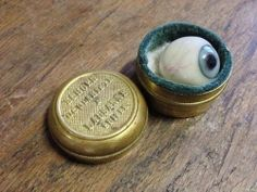 Glass eye in metal case