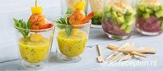 Frisse mangodip met koriander en een vleugje chili in een glaasje geserveerd met garnalen prikkers