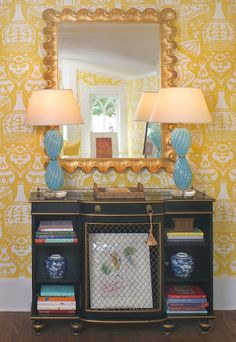 Sarah Bartholomew    A lovely vignette with a pair of blue and white scalloped slipper chairs, antique Chinoiserie cabinet, and a collecti...