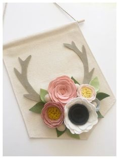 FLORAL ANTLER BANNER | Made of soft and durable wool blend felt custom ordered in the colors of your choice with a 2 week turnaround time. This sweet felt flower banner features roses, anemones, felt berries and leaves all attached to two felt deer antlers. Flowers and leaves are handmade and arranged on a 8 W X 10 L inches long natural cotton canvas banner. Banner comes ready to hang on a thin jute ribbon and has a 5 in hang length. Please refer to the color chart and leave your color…
