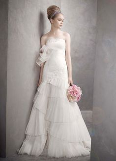 This ivory strapless dress, designed by Vera Wang, is available in a size 6, and is ivory in color.  It is a satin-faced organza fit-and-flare gown with lace appliques and has an asymmetrical pleated skirt! Priced at $399.00!(Store Style #W0379)