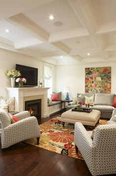 Chic colorful living room design with ivory cream walls paint color, coffered ceiling, silver gray velvet sectional sofa, mushroom linen ottoman with nailhead trim, orange black yellow floral rug, blue glass gourd lamps, silver chairs, fireplace and art.