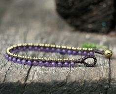 This bracelet made with 4mm amethyst semiprecious stones beads and 2.5mm brass beads woven together with dark brown wax cord and brass bell for