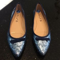 NWOT Glitter Shoes. Light blue glitter with navy trim. Never worn. Flat heel. Bow on front. Pointed toe. Back of heel is navy glitter. Unisa Shoes Flats & Loafers