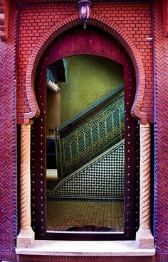 A Moorish arch and Moroccan mosaic zellij tiling at the base of the stairs and a green tadelakt (special Moroccan surface treatment) wall.