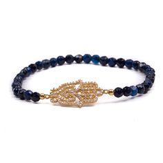 Pulseira com pedrinhas naturais na cor safira, possui o símbolo Hansa com banho de ouro e cravação de zircônias brancas.  Semijoia.