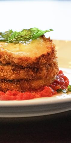 Melanzane alla Parmigiana | This succulently fried eggplant dish comes on a bed of rich San Marzano sauce, and is topped elegantly with fresh tomato and mozzarella cheese.