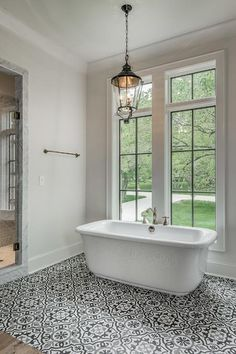 Black and white Mediterranean bathroom features a lantern hanging over a freestanding tub fitted with a deck mount tub filler placed under windows atop a white, gray and black mosaic tiled floor.