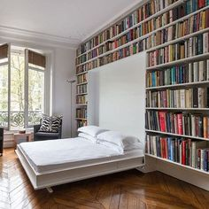 Modern Bookshelf Wall with Folding Murphy Bed. When not in use as a bedroom, the space becomes a library.