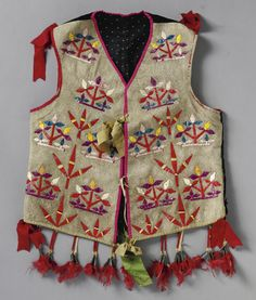 A LAKOTA QUILLED HIDE VEST composed of hide, velvet, cotton cloth, porcupine quills, silk ribbon, tin cones, and dyed chicken feathers. Length with drops 21 in.
