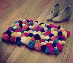 una alfombra de pompones de lana reciclada