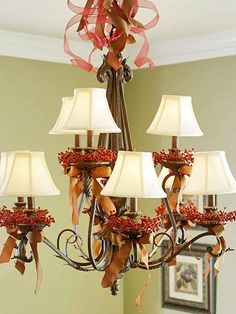 Give a dining room chandelier a Thanksgiving makeover with red berry candle rings and copper satin bows. Sheer and satin ribbon curl into a froth of holiday cheer above the decorated arms. Replace the copper ribbon with ivory for Christmas.                                                                                                                                                                                 More