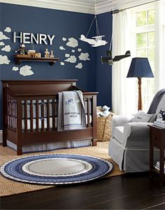 Boys Nursery- A bold navy wall color is brightened with a scattering of puffy white clouds and galvanized metal lettering in this nursery. The rich browns of the wood furniture and floor are offset by the light gray upholstery, bedding and ceiling color. In place of a traditional mobile, we hung airplanes hung from the ceiling to add a sense of movement and adventure.