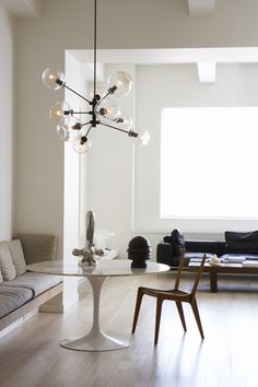 Midcentury modern furniture looks great with white saarient table and bronze chandeliers
