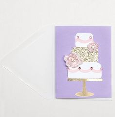 Petit Gâteau lovers unite. A mini cake card you can take wherever life takes you. Pretty pink metallic cut piping, light pink Swarovski flatbacks and tons of glitter make this mini card worthy of any occasion. Features two delectable hand made pink fabric flowers with gems in each