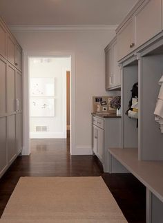 Spacious mudroom features open gray mudroom lockers atop a built-in bench with open storage below for shoes  next to a message center facing a wall of closed mudroom cabinets.