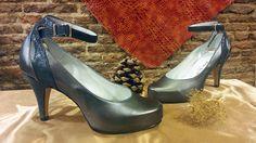 Zapatos en plata vieja y la pieza de la pulsera y el tacón en una piel grabada brillante.