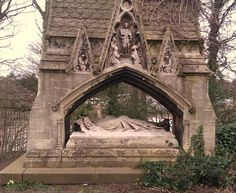 Henry Raikes, Chancellor of Chester, has one of the most extravagant tombs in the Overleigh Cemetery, featuring a full-size prone statue of the occupant protected by an ornate stone canopy. It is located in the oldest part of the cemetery on the edge of a steep drop down to the River Dee. Today, it is extensively- and picturesquely- overgrown by ivy. — in Chester, England.