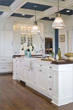 floor to ceiling cabinets, coffered ceiling, wood floors, moldings, farmhouse sink, wood countertops - blue and white kitchen......i like the blue in the ceiling