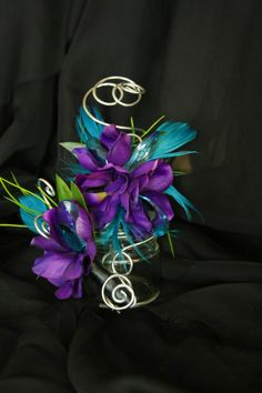 Prom, Homecoming Wrist Corsage and Boutonniere.  Purple flowers, turquoise feathers, turquoise jewels, silver wire accents. Prom flowers by Green Ambiance. www.greenambiancellc.com