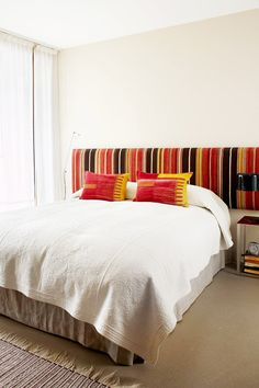 Striped and colorful headboard in white bedroom