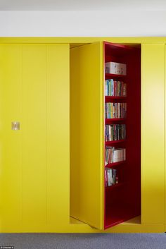 A revolving bookcase in a bright shade of yellow is one of the home's many quirky features, with the red shelves hidden Grand Designs Channel 4, Revolving Bookcase, Tall Cabinet Storage, Locker Storage, Snug Room, Hidden Rooms, Home Tv, Kitchen Styling, Black House