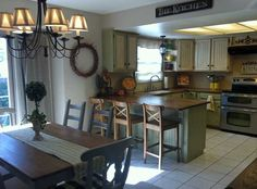 Kitchen table, Drapes over the patio door, countertop on peninsula hanging over with bar stools, Two toned upper vs lower cabinets, microwave over stove, wood countertops