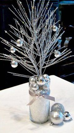New Years Eve decor - silver branches with fake snow and silver ornaments. This would be cute with mini disco balls!
