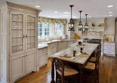A ceiling-to-floor cabinet with fabric-covered glass doors and wrought-iron pendant lamps bring in French country flair. The angular kitchen island follows the lines of the perimeter cabinets and bay window.