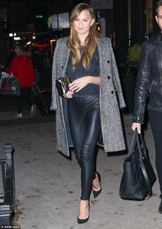 Sexy style: Chrissy Teigen stunned in black leather-like leggings, as she left her New Yor...