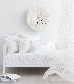 A feather headdress adds a much needed texture while providing interest and focal point in an all white modern room.