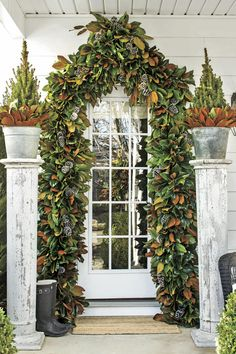 Attention-Grabbing Archway - These Porches Got a Merry Makeover for the Holidays - Southernliving. This archway combines a few of the South's quintessential Christmas greenery, like pinecones and magnolia leaves, for a show-stopping entryway.