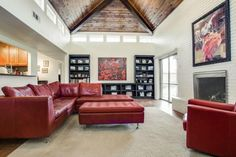 Cool living room space // Red leather couch, vaulted wood ceiling, white brick fireplace