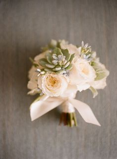 A soft bouquet of succulents and white garden roses is the perfect collection of rustic blooms for an outdoor wedding.