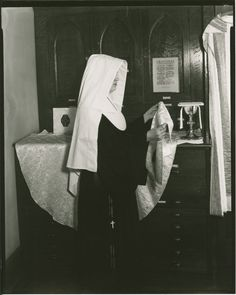 Sister of Mercy, perhaps a novice, preparing altar cloths in the sacristy for Mass. Also in the photo are a chalice, some vestments (far right), and a page of prayers in Latin (Orationes) that a priest would recite while vesting. Dated 1955.