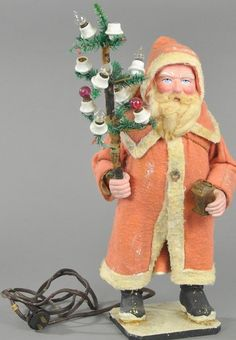 """A seldom seen example, this Santa is wearing a red felt robe with white trim, composition feet, hands and face with kind blue eyes, fur beard, wearing a woven brass basket on his back and holding an electric light feather tree missing two bulbs in one hand, brass lantern in other, not electrified, wire brittle. 17"""" h."""
