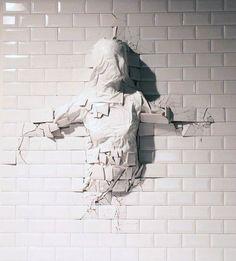 http://beautifuldecay.com/2014/09/25/graziano-locatellis-sculptures-emerge-beneath-walls/