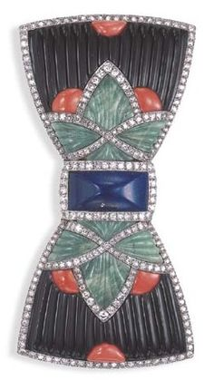 A RARE ART DECO HARDSTONE AND DIAMOND DEVANT DE CORSAGE, BY BOUCHERON | Mosaic design | Sculpted onyx ribbon bow | Decorated with fluted jade foliate motifs | Carved coral accents | The central carved lapis lazuli knot with circular and single-cut diamond trim | Mounted in 18k white gold | circa 1925 | Signed Boucheron, Paris | Desiged by Lucien Hirtz | Mounted by Bisson.
