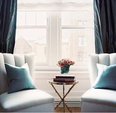 House Beautiful - living rooms - tripod gold side table, tripod gilt side table, round gold side table, stacked books, vase of flowers, blue...